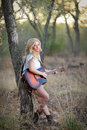 Country girl with acoustic guitar beautiful blond woman playing an outdoors in a cottonwood forest Stock Photo