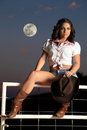 Country girl at dusk beautiful sexy sitting on a white pipe fence holding her cowboy hat with the moon in the sky behind her Stock Images
