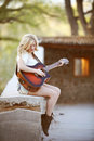 Country girl guitar music beautiful blonde playing a while sitting on a concrete ledge Royalty Free Stock Photography