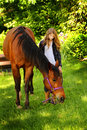 Country girl loves horse a teenage with long wavy blond hair standing with a on a lead rope shallow depth of field Stock Image