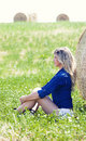 Country girl near a haystack green lawn young is sitting bale of hay in outdoors the is in profile sitting on the floor with her Stock Photo