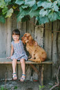 Country girl sitting on a bench with her dog under vine. wooden Royalty Free Stock Photo