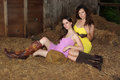 Country girls in a barn two beautiful wearing colorful dresses cowboy boots and western hat Royalty Free Stock Photos
