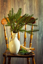 Country house interior chair with homemade christmas crackers and vase of pine branches Stock Image