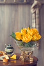 Country house interior reception hall with table adorned with yellow roses in an antique vase Royalty Free Stock Photo