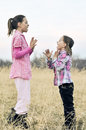 Country kids playing girls patty cake outside Royalty Free Stock Images