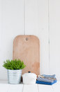 Country kitchen decoration cottage life a house plant in a metal pot pottery utensils and napkins on white painted board Royalty Free Stock Photo