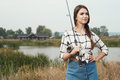 Country lady standing against pond on ranch with fish rod cute rural brown haired posing house and fishing she stands in grass Stock Photos