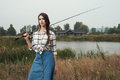 Country lady standing against pond on ranch with fish rod cute rural brown haired posing house and fishing she stands in grass Royalty Free Stock Photo