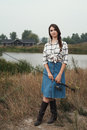 Country lady standing against pond on ranch with fish rod cute rural brown haired posing house and fishing she stands in grass Stock Image