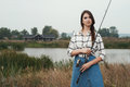 Country lady standing against pond on ranch with fish rod cute rural brown haired posing house and fishing she stands in grass Royalty Free Stock Photography