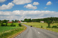Country landscape with a road and farms Stock Photos