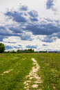A country road and a cloud of clouds in the sky. Rural landscape Royalty Free Stock Photo