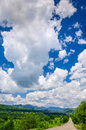 Country road mountains clouds Royalty Free Stock Photo