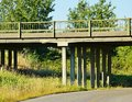 Country road overpass quiet with a cement surrounded by grasses and trees Stock Photo