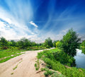Country road and river calm cloudy sky Royalty Free Stock Photos