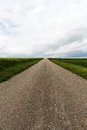 Country road to nowhere street with horizon and cloudscape Royalty Free Stock Image