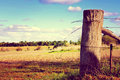 Country side scene with old gate post and barb wire retro sunset filter style taken at barossa valley south australia Royalty Free Stock Image