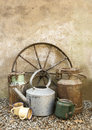Country still life with old copper milk urns a metal wagon wheel cups and lidless distressed vintage metal kettle and teapot Royalty Free Stock Images