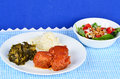Country style meatballs cooking in tomato sauce on white plate with mashed potatoes and collard greens against blue gingham Royalty Free Stock Image