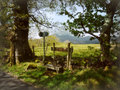 Country walk photograph of a stile with footpath signs trees fields and mountains Stock Photo