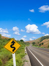 Country winding road sign with blue sky Royalty Free Stock Photo