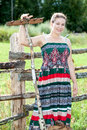 Country woman standing with rakes behind fence in sundress Royalty Free Stock Photo