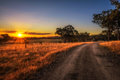 Countryside landscape with rural dirt road at sunset in Australia Royalty Free Stock Photo