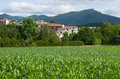 Countryside in pays basque there are a green field white houses of the town and remote dark mouintains Stock Photos