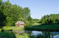Countryside with wooden bathhouse and green nature Royalty Free Stock Photo