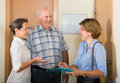 Couple answering questions of employee in door mature the young visitor at home Stock Photography
