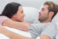 Couple awaking and looking at each other in bed Royalty Free Stock Images