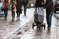 Couple with a baby buggy in the rainy city Stock Photos