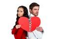 Couple back to back holding heart halves against white background Royalty Free Stock Photo