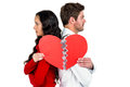 Couple back to back holding heart halves on white background Stock Photography