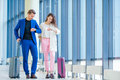 Couple with baggage in international airport hurrying for a flight to land. Man and woman looking on their clock indoor Royalty Free Stock Photo