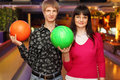 Couple with balls stand in bowling club Royalty Free Stock Photo