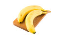 A couple of bananas on cutting board isolated on white background Stock Photo