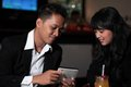 Couple at bar photograph of relaxing or lounge looking tablet Stock Photo