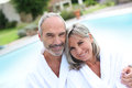 Couple in bathrobe relaxing in spa hotel happy senior by resort pool Royalty Free Stock Photos