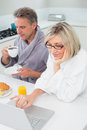 Couple in bathrobes with coffee and juice using laptop in kitchen the at home Stock Photos