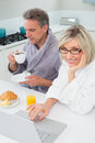 Couple in bathrobes with coffee and juice using laptop in kitchen the at home Royalty Free Stock Photo