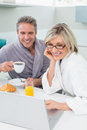 Couple in bathrobes with coffee and juice using laptop the kitchen at home Stock Images