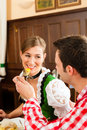 Couple in Bavarian Tracht eating in restaurant Stock Photo