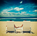 Couple in beach chairs holding hands near ocean cross process vintage style Stock Photography