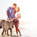 Couple on the beach with dog kissing photo of a each other shot in square composition copyspace Stock Photo