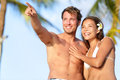 Couple on beach happy in swimwear man pointing men showing and looking at view beautiful young multi ethnic asian women and Royalty Free Stock Photo