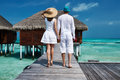 Couple on a beach jetty at maldives tropical Stock Image