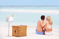 Couple on beach with luxury champagne picnic relaxing Royalty Free Stock Images