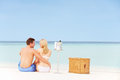 Couple on beach with luxury champagne picnic sitting dowm Royalty Free Stock Photography